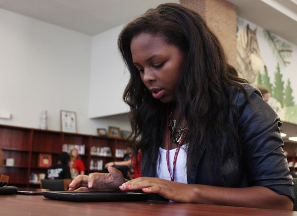 In the library, Ta'Quell McKenzie switches out her iPad 2 for the iPad 3 Mini, during the second week of school.