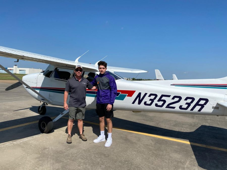 Junior Jordan Duran standing with his flight instructor after flying solo.