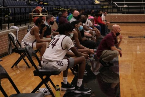 Basketball players watching the game on the sideline.