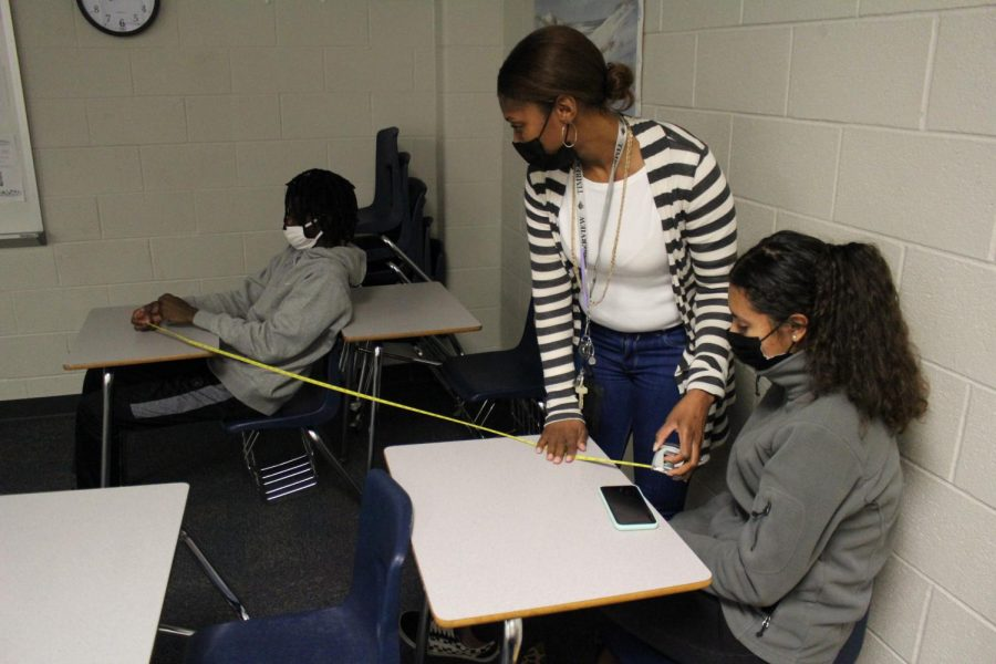 Ms. Tanner measures the distance between desks.